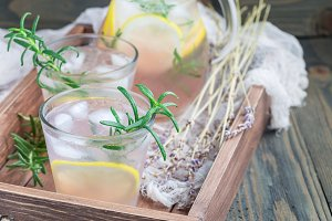 Homemade lemonade with lavender, fresh lemons and rosemary on wooden background, horizontal, copy space