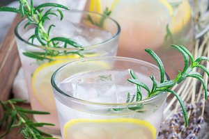 Homemade lemonade with lavender, fresh lemons and rosemary on wooden tray, vertical