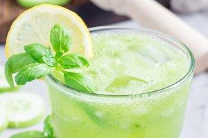 Healthy homemade lemonade with cucumber, basil, lemon, honey, sparkling water, vertical