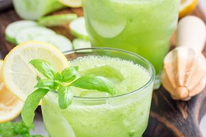 Healthy homemade lemonade with cucumber, basil, lemon, honey, sparkling water, vertical