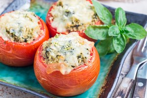 Homemade baked tomato stuffed with quinoa and spinach topped with melted cheese on the plate, horizontal