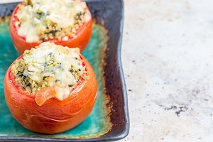 Baked tomatoes stuffed with quinoa and spinach topped with melted cheese on plate, horizontal, copy space
