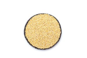 Organic millet groats in metal bowl, top view, isolated