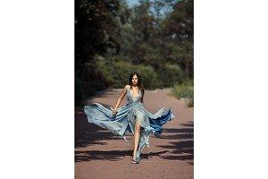 Young beautiful woman blue dress walking path in park.