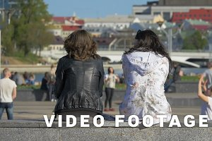 Two girlfriends relax in the city and watch sport games - slowmo 180 fps
