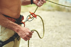man belaying other climber through a belay device.