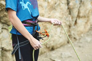 woman belaying other climber through a belay device.