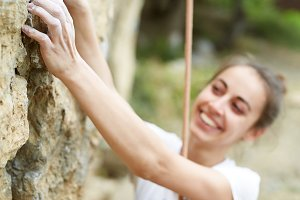 smiling woman climber is preparing to scale the rock