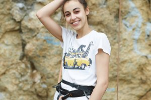 smiling woman in climbing harness posing against the cliff