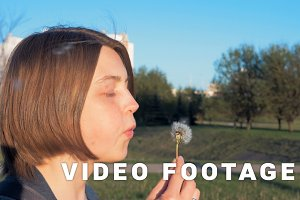 Young girl blows off the dandelion - slowmo 180 fps