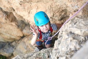 a little boy climbs on rock