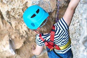 a little boy climbs on rock
