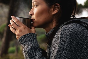 Young asian female hiker drinking