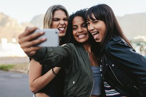 Smiling girls making selfie