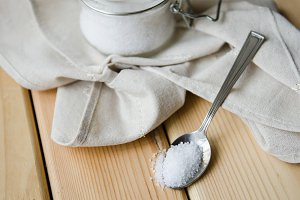 White sea salt white napkin in a jar on an iron spoon