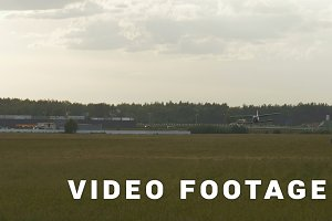 Small airplane lands on the grass field - slowmotion 60 fps