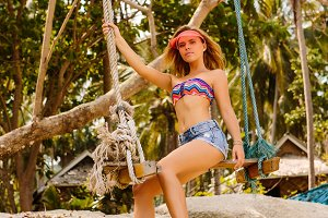 Beautiful woman posing on swings.