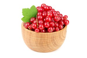Red currant berries in a wooden bowl with leaf isolated on white background