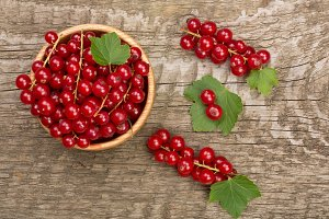 Red currant berries in a wooden bowl with leaf on the old wooden background. Top view