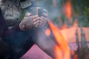 Hands in mitts holding hot tea cup outdoor near bonfire