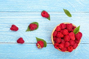 Raspberries in a bowl on the blue wooden background. Top view
