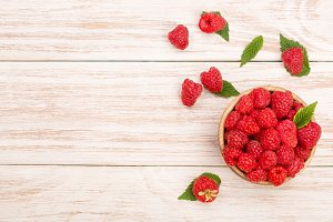 Raspberries in a bowl on the light wooden background with copy space for your text. Top view
