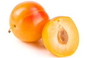 Yellow plum and half isolated on white background