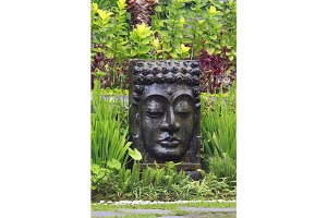 Buddha image with falling water in the tropical garden in Ubud, Bali.