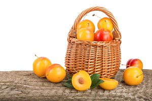 Yellow plums in a wicker basket on wooden table with white background