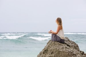 Girl sit at the seaside on the rock and meditating in yoga woman pose