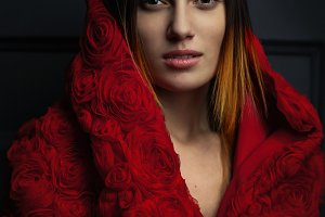 beautiful woman red cloak with red flowers roses in studio