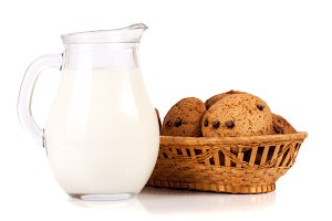 jug of milk with oatmeal cookies in a wicker basket isolated on white background
