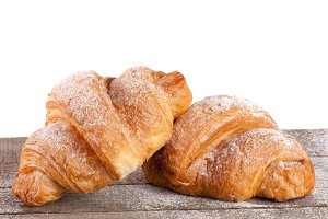 two croissant sprinkled with powdered sugar on a wooden table with white background