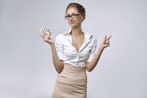 A business lady holds a little money in her right hand and her left hand shows that there is very little money.