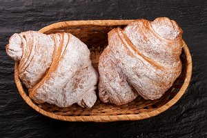 two croissant sprinkled with powdered sugar in a wicker basket on black stone background closeup. Top view