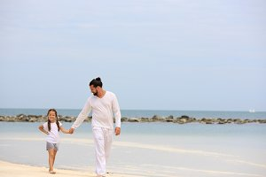 Father and daughter walking on deserted tropical beach together happy loving vacation