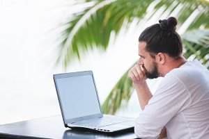 Man relaxing on the beach with laptop, freelancer workplace, dream job