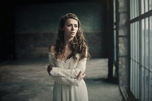 Beautiful girl in in white vintage dress with curly hair posing near the loft window. Woman in retro dress. Worried sensual emotion . Retro fashion