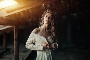 Beautiful girl in in white vintage dress with curly hair posing on the attic. Woman in retro dress. Worried sensual emotion . Retro fashion