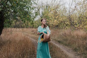 Romantic woman wearing long elegant dress standing on the field, autumn season, relaxation in countryside, enjoying nature, pleasure concept