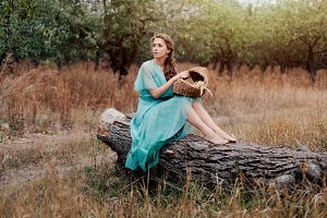 Romantic woman wearing long elegant dress sitting on the field, autumn season, relaxation in countryside, enjoying nature, pleasure concept