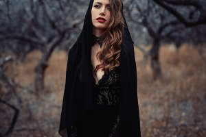 Beautiful girl in in black vintage dress with curly hair posing in the woods. Woman in retro dress lost in the forest. Worried sensual emotion . Retro fashion
