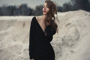 Beautiful girl in in black vintage dress with curly hair posing on the sand. Woman in retro dres. Worried sensual emotion . Retro fashion.