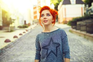 Young redhead woman looking up standing on the urban street