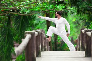 man doing yoga in tropic jungle bridge