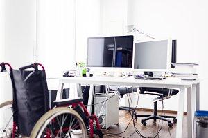 Empty Wheelchair In Front Of Desk In Modern Office