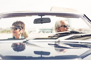 Senior Couple Driving A Convertible Classic Car