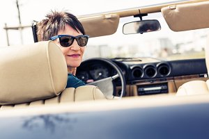 Senior Woman Driving A Convertible Classic Car