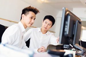 Young Asian Office Workers At Their Desk