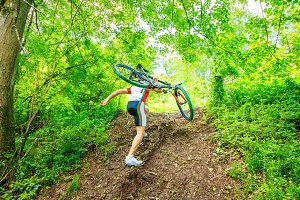 Young Man Carrying His Mountain Bike Uphill